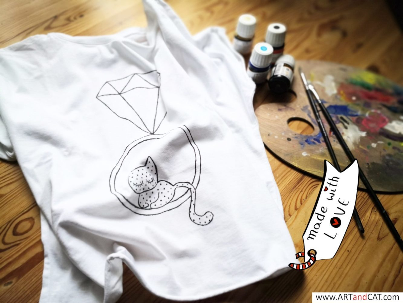 white cotton hand painted cats lovers t-shirt on table with paintings and brushes