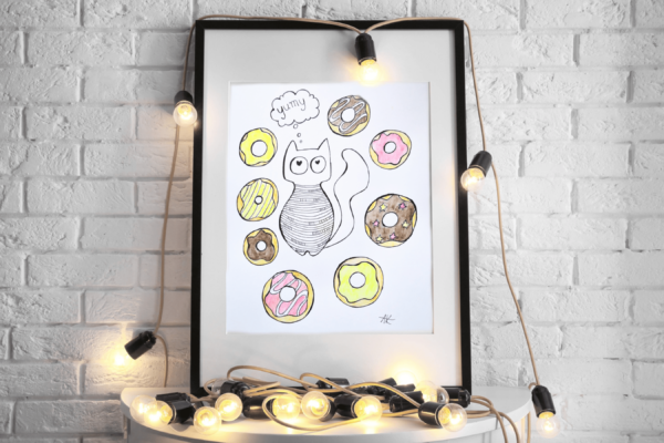 handicraft graphic with fat cat and colorful donuts standing on commode with decorative lamps