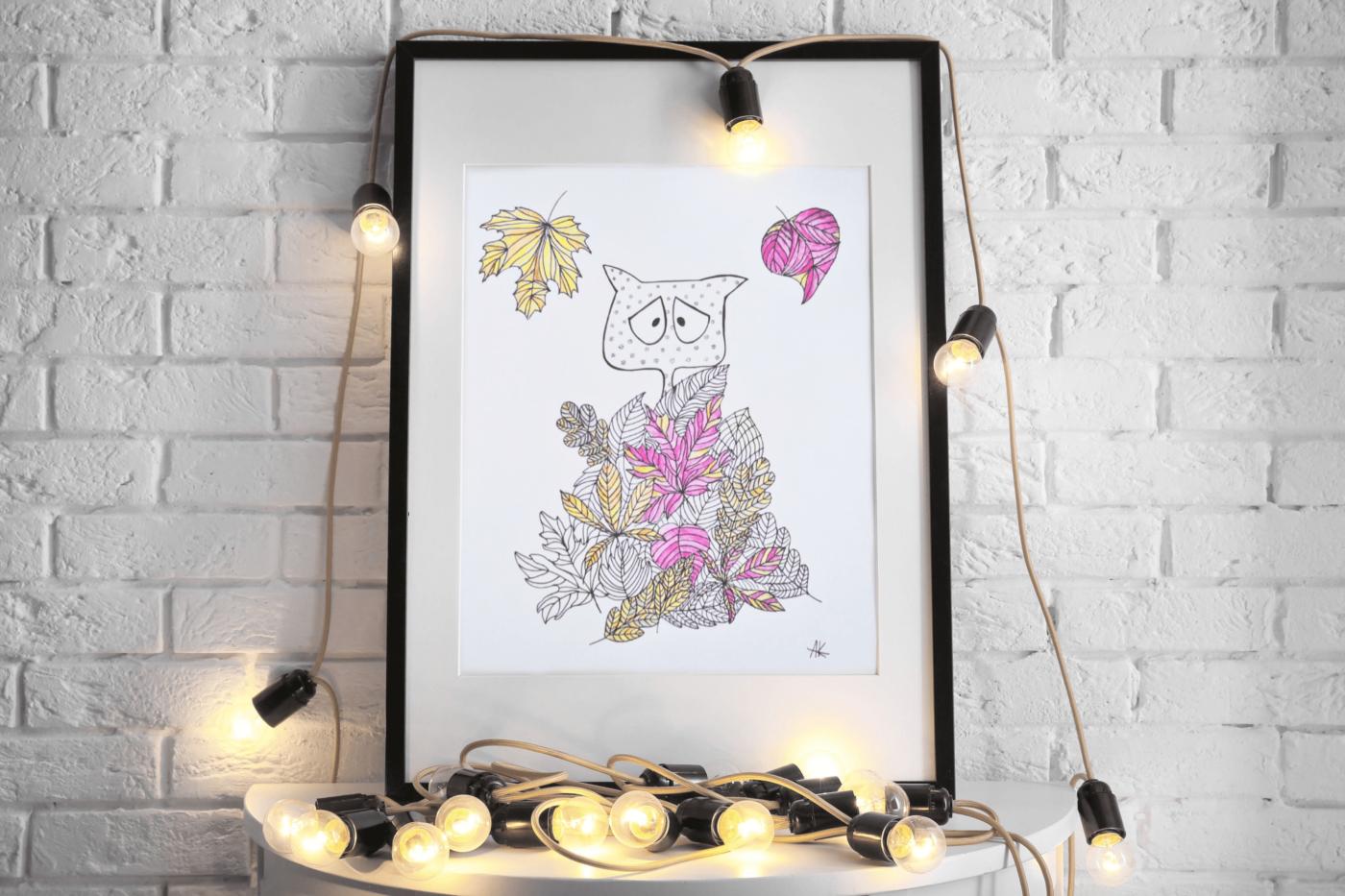 ręcznie robiona grafika z kotem w jesiennych liściach stojąca na komodzie z lampkami przytulne wnętrze