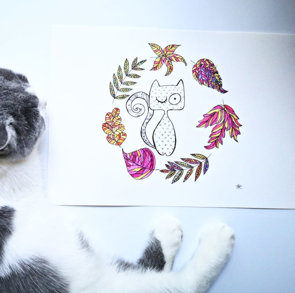 british cat sleeping next to handicraft drawing with funny cat and autumn leaves