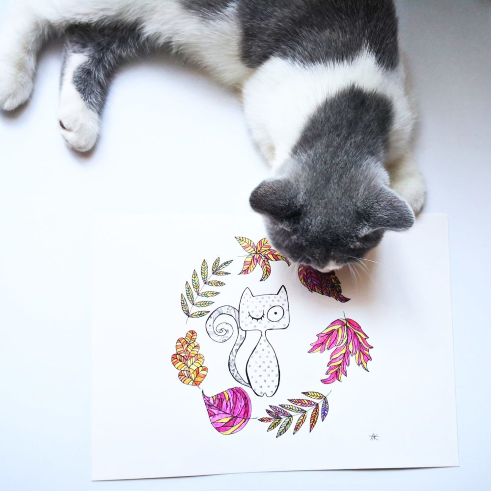 kot brytyjski śpiący obok ręcznie robionej grafiki z zabawnym kotem i jesiennymi liścmi